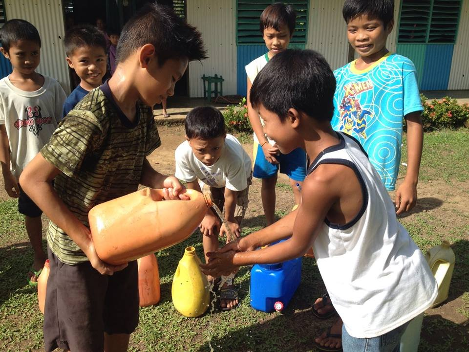 Children washing hands using clean water at school.
